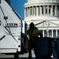 A trash collector removes garbage from Capitol Hill as the U.S. government remains shut down Saturday in Washington.   AFP-JIJI