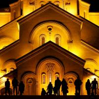 People walk in front of the Holy Trinity cathedral for a midnight Christmas service in Tbilisi, Georgia, early on Sunday. | REUTERS