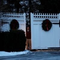 A man is seen at the gate to the home of former U.S. President Bill Clinton and former Democratic presidential candidate Hillary Clinton after firefighters were called to put out a fire at the property in Chappaqua, New York, Wednesday. | REUTERS