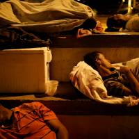 People sleep in a sports center, where a community of homeless Venezuelan migrants stays, in Cucuta, Colombia, Wednesday. | REUTERS