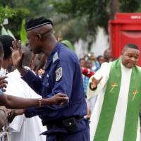Riot policemen attempt to block a Catholic priest and demonstrators during a protest against President Joseph Kabila, organized by the Catholic church in Kinshasa Sunday. | REUTERS