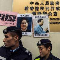 Police walk past a missing person notice for bookseller Gui Minhai (left) posted on top of the sign for China's Liaison Office in Hong Kong in January 2016. Rights campaigners have slammed as 'appalling' reports that Gui has been snatched again in mainland China, the latest person ensnared in Beijing's crackdown on civil society. | AFP-JIJI