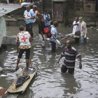 Rescue workers remove bodies of children following floods in Kinshasa, Democratic Republic of Congo, on Jan. 4.   AP