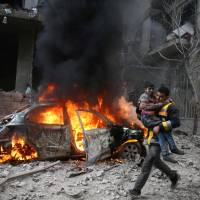 A Syria Civil Defense member carries a wounded child in the besieged town of Hamoria, eastern Ghouta, in Damascus Saturday. | REUTERS