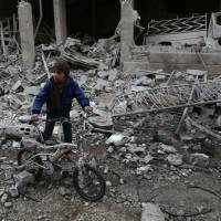 A Syrian boy walks with a bike amid the rubble following reported bombardment by Syrian and Russian forces in the rebel-held town of Hamouria, in eastern Ghouta, on Saturday. Regime and Russian airstrikes on a rebel-held enclave near the Syrian capital killed at least 17 civilians, a war monitor said. | AFP-JIJI