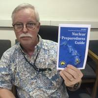 Toby Clairmont, the Hawaii Emergency Management Agency's executive officer, shows new informational materials to a reporter in Honolulu last July.   AP