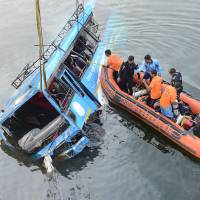 Indian police rescue people after a bus accident at the Ghogra Canal in Murshidabad district, around 187 miles from Kolkata, on Monday. At least 36 people were killed in eastern India's West Bengal state early Monday after the speeding passenger bus swerved off a bridge and plunged into the river, police said. | AFP-JIJI