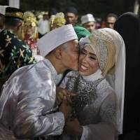 A groom kisses his bride during a mass wedding held in celebration of the New Year in Jakarta Sunday. Hundreds of couples took part in the mass marriage held by the city government to help the poor who were unable to afford a proper wedding. | AP