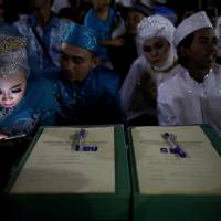 A bride looks at her mobile phone while taking part in a mass wedding organised by the city government as part of New Year's Eve celebrations in Jakarta Sunday. | REUTERS