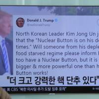 People watch a TV news program showing the Twitter post of U.S. President Donald Trump while reporting North Korea's nuclear issue, at Seoul Railway Station in Seoul Wednesday. Trump boasted that he has a bigger and more powerful 'nuclear button' than North Korean leader Kim Jong Un does — but the president doesn't actually have a physical button. The letters on the screen read: 'More powerful nuclear button.' | AP
