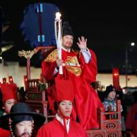 A torchbearer wearing a traditional costume carries the Olympic torch in Seoul on Saturday. | REUTERS