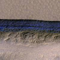 A cross-section of a thick sheet of underground ice is exposed at the steep slope that appears bright blue in this enhanced-color view of Mars from the High Resolution Imaging Science Experiment (HiRISE) camera on NASA's Mars Reconnaissance Orbiter in this image released on Thursday. | NASA / JPL-CALTECH / UA / USGS / HANDOUT / VIA REUTERS