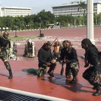 Indonesian special forces conduct a snake-handling demonstration for U.S. Defense Secretary Jim Mattis on Wednesday in Jakarta.   AP