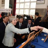 U.K.'s May walks tightrope between trade and politics on trip to China