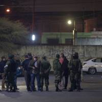 Members of the Mexican army monitor the area where seven people were killed inside a house while they were watching a soccer game in Monterrey, Mexico, Sunday.   AFP-JIJI