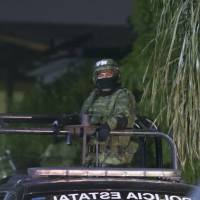 A member of the Mexican army patrols the area where seven people were killed inside a house while they were watching a soccer game in Monterrey, Mexico, Sunday.   AFP-JIJI