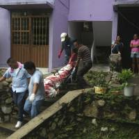 A body wrapped in a bloodstained sheet is removed from an apartment building where a woman and two men were executed, in the Alta Progreso neighborhood of Acapulco, Mexico, last August. Both men were bound with tape, and all three were shot in the head at an apartment outfitted as an office for a taxi service. Mexico's Interior Department posted on Sunday that the country's homicide rate is the highest in decades. | AP