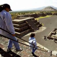 Tourists walk down the Pyramid of the Moon in the ancient city of Teotihuacan, Mexico, in October 2000. | AP