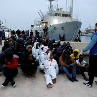 Migrants sit at a naval base after they were rescued by Libyan coast guard boats, in Tripoli Tuesday. | REUTERS