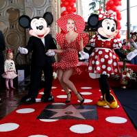 Singer Katy Perry poses with the characters of Mickey Mouse and Minnie Mouse at the unveiling of the star for Minnie Mouse on the Hollywood Walk of Fame in Los Angeles Monday. | REUTERS