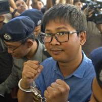 Reuters journalist Wa Lone is escorted by police upon his arrival at a court Wednesday on the outskirts of Yangon. | AP