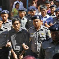 Myanmar police officers escort detained Reuters journalists Kyaw Soe Oo (second from left) and Wa Lone (fourth from left in back row) from a court after a hearing in Yangon, Myanmar, on Tuesday. | AP