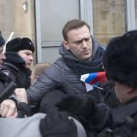 Russian opposition leader Alexei Navalny is detained by police officers in Moscow Sunday. Opposition politician Navalny called for nationwide protests following Russia's Central Election Commission's decision to ban his presidential candidacy. | AP