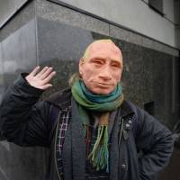 A supporter of opposition leader Alexei Navalny wearing a rubber mask depicting President Vladimir Putin takes part in a rally calling for a boycott of March 18 presidential elections, Sunday in St. Petersburg. | AFP-JIJI