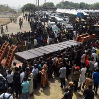 Coffins arrive at Ibrahim Babanginda Square in the Benue State capital Makurdi Thursday during a funeral service for scores who died following clashes between Fulani herdsmen and natives of Guma and Logo districts. Violence between the mainly Muslim Fulani herdsmen and Christian farmers has claimed thousands of lives across Nigeria's central states over the past few decades. The conflict is being driven by an increasing need for resources — primarily land and water — and is often exacerbated by ethnic and sectarian grievances. | AFP-JIJI
