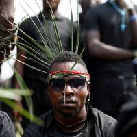 A man wears palmleaves on his head during the funeral mass organized for victims of the Fulani herdsmen's killlings, in Makurdi, Nigeria, Thursday. | REUTERS