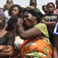 A woman cries as the casket of a relative is brought to Ibrahim Babanginda Square in the Benue State capital Makurdi Thursday during a funeral service for scores who died following clashes between Fulani herdsmen and natives of Guma and Logo districts. | AFP-JIJI
