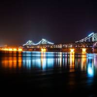 Spotlight beams are seen from the North Korean town of Sinuiju, past the Friendship Bridge and Broken Bridge, as seen from Dandong, in China's northeastern Liaoning province, on Wednesday. | AFP-JIJI