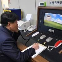 A South Korean government official communicates with a North Korean officer Wednesday on the dedicated hotline at the border village of Panmunjom. | AP