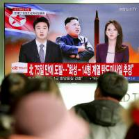 People watch a TV news report in Seoul discussing North Korea's test-firing of an intercontinental ballistic missile that landed close to Japan on Nov. 29. | REUTERS