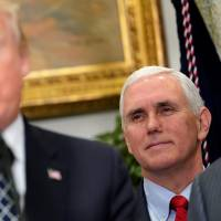 U.S. Vice President Mike Pence watches as President Donald Trump speaks before signing a proclamation to honor Martin Luther King Jr. in the Roosevelt Room of the White House in Washington on Jan. 12. | REUTERS