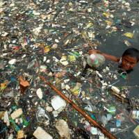 A boy collects plastic for resale at Marunda beach in Jakarta in 2007. | REUTERS