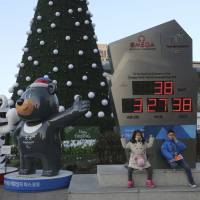 Children pose Tuesday in Seoul in front of an electric board that shows the number of days left until the opening of the Pyeongchang Winter Olympic Games and beside the official mascots, the white tiger Soohorang for the Olympics and the black bear Bandabi for the Paralympics. | AP