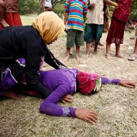 A Rohingya refugee woman ties to console another woman, who just received news that her husband was killed in Myanmar, in Cox's Bazar, Bangladesh, last August. | REUTERS