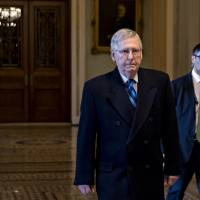 Senate Majority Leader Mitch McConnell, a Republican from Kentucky, walks toward his office at the U.S. Capitol in Washington on Sunday. The House and Senate were back in session Sunday with a federal government shutdown in its second day amid a spending-bill impasse in Congress. | BLOOMBERG
