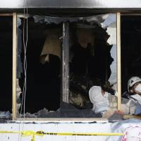 Police investigators inspect a hospital after a fire in Miryang, South Korea, on Saturday. | AP