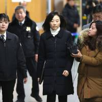 Former South Korean culture minister Cho Yoon-sun (center) arrives for a court appearance in Seoul on Tuesday. | AFP-JIJI