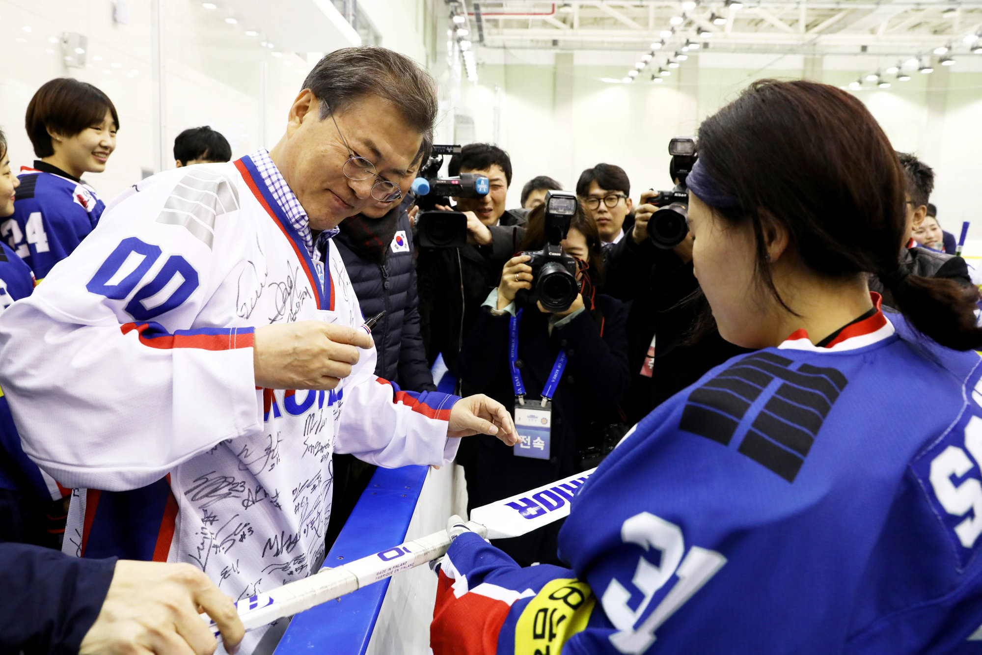 South Korean President Moon Jae-in signs an autograph Wednesday on an ice hockey stick during his visit to Jincheon National Training Center in South Korea. | REUTERS