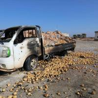 Trucks loaded with sacks of potatoes stand abandoned Monday after their windows were blasted from their frames following airstrikes by government forces that hit the vegetable market of the town of Saraqeb in Syria's northwestern province of Idlib. | AFP-JIJI