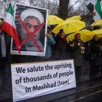 Opponents of Iranian President Hassan Rouhani hold a protest outside the Iranian Embassy in west London Sunday. | REUTERS