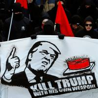 Protesters with banners march during an anti-World Economic Forum and anti-U.S. President Donald Trump demonstration in Bern, Switzerland, on Saturday ahead of his visit to the World Economic Forum later this month. | REUTERS