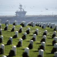 The nuclear-powered aircraft carrier USS Carl Vinson passes Fort Rosecrans National Military Cemetery as it leaves San Diego Bay for deployment to the Western Pacific Friday. More than 6000 sailors assigned to the strike group departed Friday, as part of a regularly scheduled deployment. | AP
