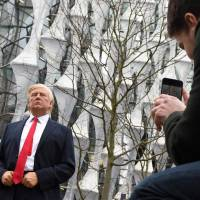 Pedestrians take pictures of a Madame Tussauds wax figure of U.S. President Donald Trump outside the new American Embassy in Embassy Gardens, southwest London, on Friday. | AFP-JIJI