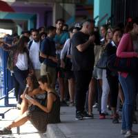 People line up in Buenos Aires on Wednesday during a vaccination campaign for yellow fever, dengue, chikungunya and Zika after the World Health Organization issued recommendations for travelers heading to certain parts of Brazil and Southeast Asia. | REUTERS