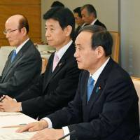 Chief Cabinet Secretary Yoshihide Suga (right) speaks Tuesday at the Prime Minister's Office in Tokyo. . | KYODO