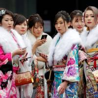 Women wearing kimono attend their Coming-of-Age Day celebration ceremony at an amusement park in Tokyo on Jan. 8. According to data provided by the 23 ward offices, 10,959 new non-Japanese adults live in central Tokyo, or 13 percent of the 83,764 new adults living in the city. | REUTERS